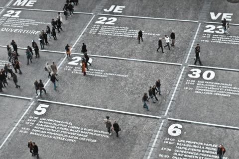 People walking over a calendar painted on a public square